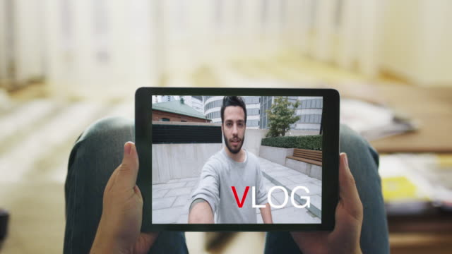 Casual Man Lying on His Couch Watching Fashionable Video Blogg on His Tablet Computer. Inscription 'Vlog' appears on the Screen. Point of View Shot. video