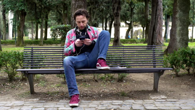 casual man on the bench listening to music with his smartphone - bench stock videos & royalty-free footage