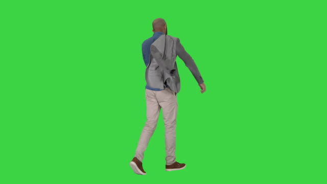casual man putting blazer on it is getting cold on a green screen, chroma key - точка съёмки стоковые видео и кадры b-roll