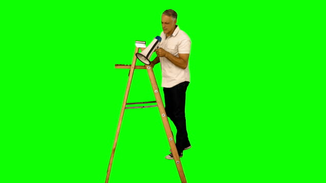 stockvideo's en b-roll-footage met casual man standing on ladder and shouting - ladder