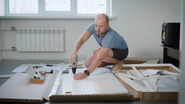 Casual man wearing blue tshirt and black shorts assembling new table for his flat Casual man wearing blue tshirt and black shorts assembling new table for his flat. He is using electric screwdriver. handbook stock videos & royalty-free footage