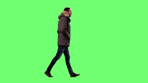 casual man wearing winter clothes / jacket cammina felicemente su uno schermo verde mock-up sullo sfondo. - abbigliamento casual video stock e b–roll