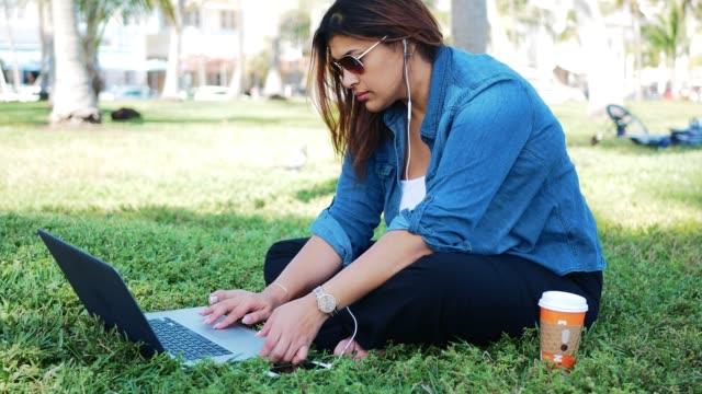 캐주얼 천년 라티나 공원 미국에서 노트북을 사용 하 여 - 몸매 관심 스톡 비디오 및 b-롤 화면