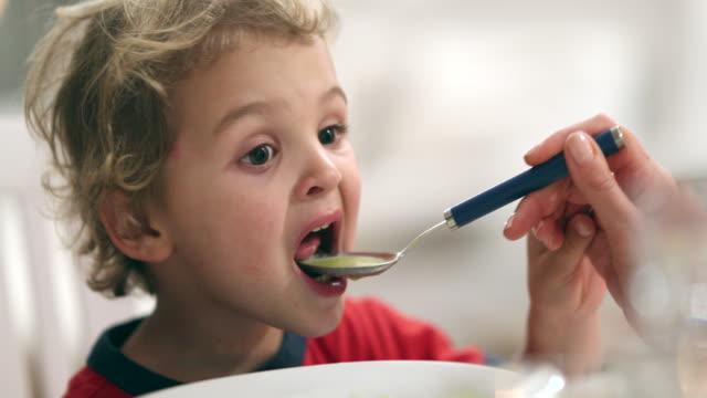 vidéos et rushes de scène occasionnelle de petit garçon étant alimenté la soupe par la maman - manger