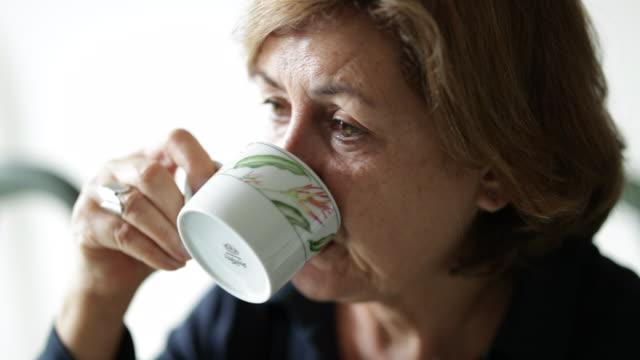 Casual woman taking a sip of coffee at breakfast table