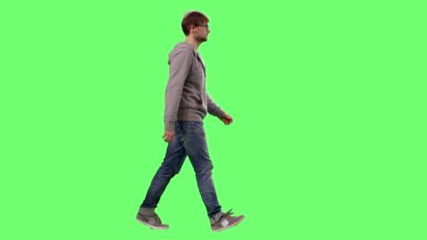 vidéos et rushes de casual jeune adulte marchant sur un fond d'écran vert de maquette. - marcher