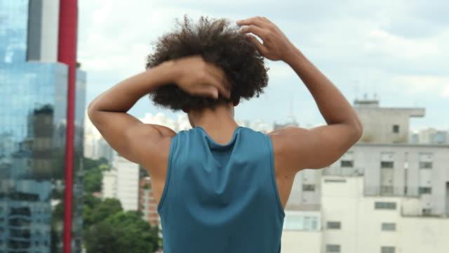 bina görünümü üstünde şehir manzara bakan iken afro saç ayarlayarak casual genç siyah afrikalı adam - ayarlamak stok videoları ve detay görüntü çekimi
