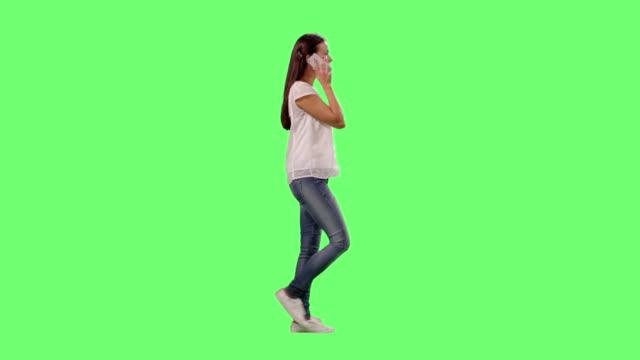 vídeos de stock, filmes e b-roll de casual jovem morena garota está andando e falando sobre o smartphone em uma tela verde de mock-up em segundo plano. - fundo verde