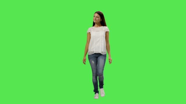 casual young brunette girl is walking on a mock-up green screen in the background. - brązowe włosy filmów i materiałów b-roll