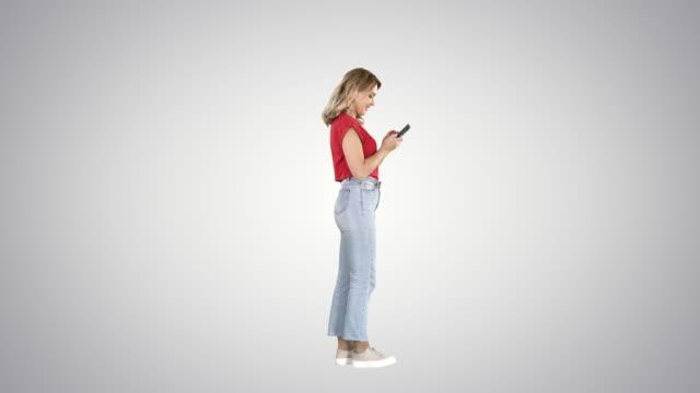 グラデーションの背景に携帯電話でタイピングカジュアル若い女性 - 全身点の映像素材/bロール
