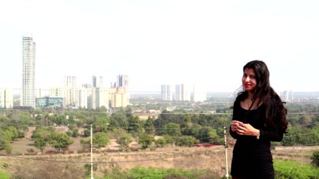 Casual young women standing near city buildings 4K Video : - Casual young teenage girl standing near skyscraper in Gurugram, (Haryana), India. haryana stock videos & royalty-free footage