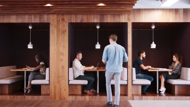Casually Dressed Businessmen And Businesswomen Meeting And Working In Cubicles In Modern Office Shot In Slow Motion Businesspeople working and having informal meetings in cubicle area of modern office - shot in slow motion office cubicle stock videos & royalty-free footage