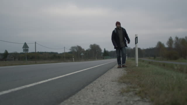 Casualy Dressed Traveler Walking along the Highway at a Cloudy Day. video