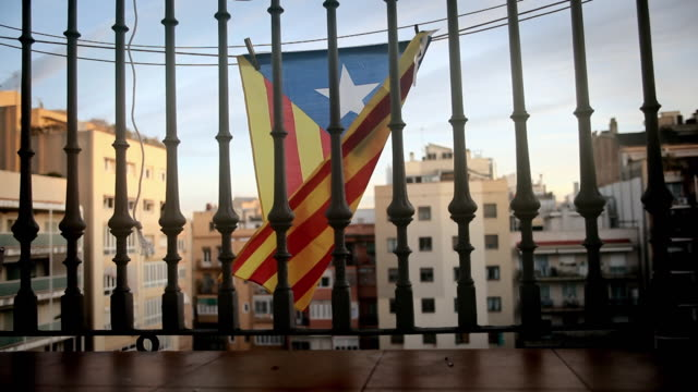 Catalan independence. Independence flag on a Barcelona balcony. Catalonia.  Bandera independetista catalana en un balcón de Barcelona. Estelada Catalan independence Independence flag behind the bars of a balcony in  independence stock videos & royalty-free footage