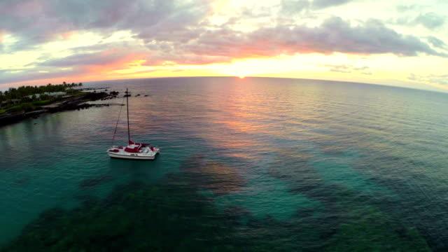 Catamaran at Sunset Aerial An aerial sunset shot with a catamaran in the ocean. big island hawaii islands stock videos & royalty-free footage