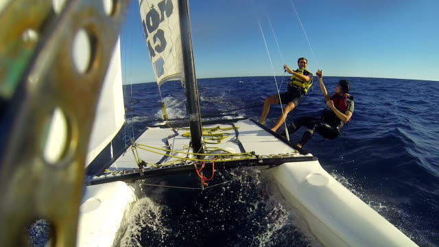 vídeos de stock e filmes b-roll de catamaran under sail at high speed, people aside the hull high-fiving each other - veleiro