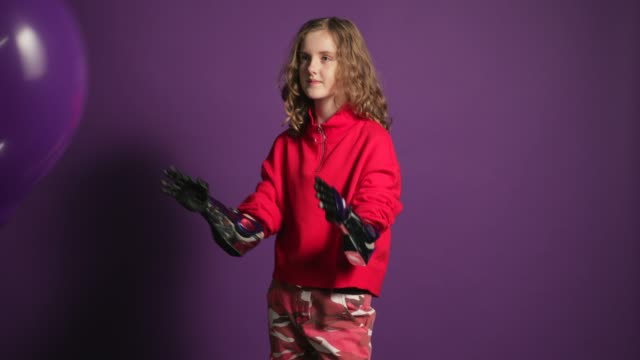 Catching a Balloon Teenage girl with prosthetic arms standing infront of a coloured background. She is holding a big purple balloon. prosthetic equipment stock videos & royalty-free footage