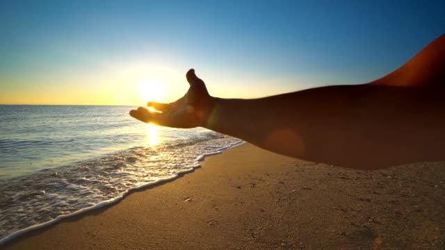 日没時に男の手から太陽を捕まえる - 指点の映像素材/bロール