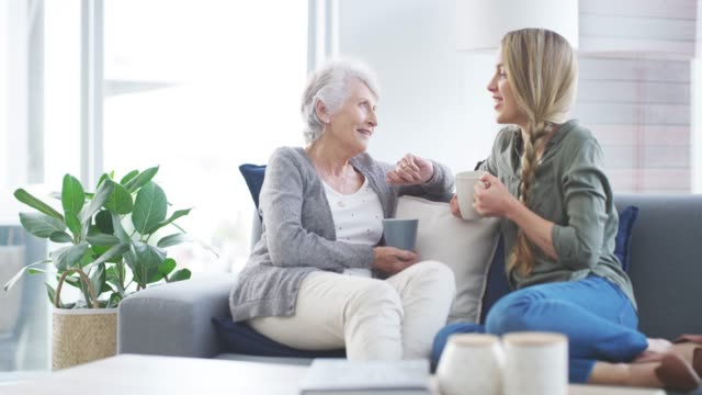Catching up over a good cuppa 4k video footage of a young woman bonding with her elderly mother at home coffee break stock videos & royalty-free footage