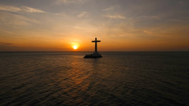 Catholic cross in the sea at sunset video