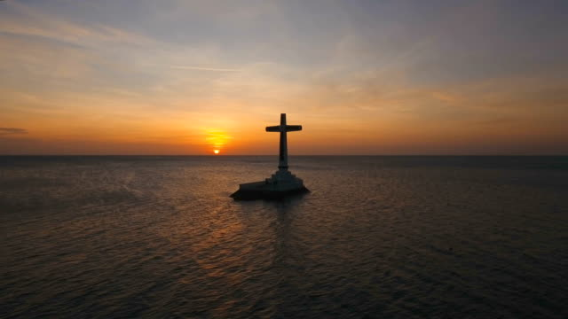Catholic cross in the sea at sunset