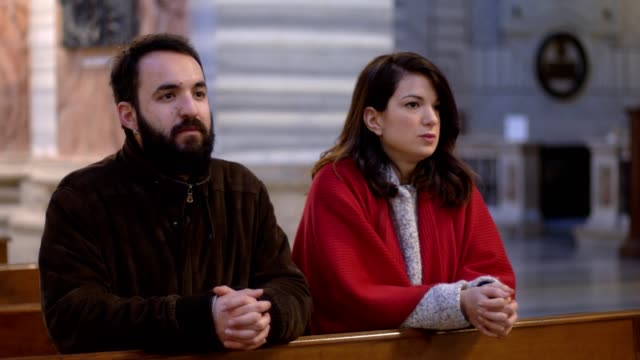 catholic married couple praying in church to have a child - mano donna dita unite video stock e b–roll