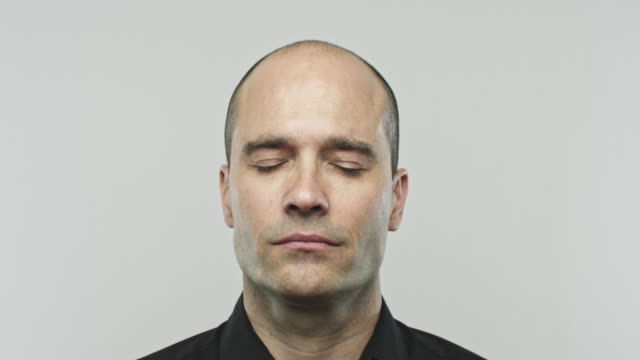 Caucasian adult man closing eyes Close up video portrait of a bald man closing his eyes. Footage of real caucasian man with blank expression against gray background. Studio 4K RAW video with sharp focus on eyes. eyes closed videos stock videos & royalty-free footage