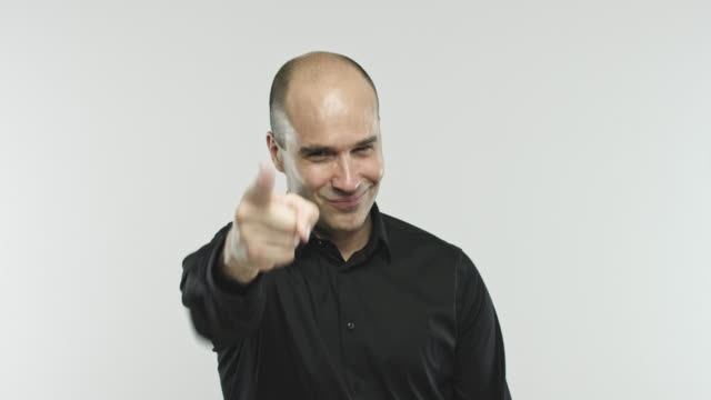 Caucasian adult man pointing at camera Video portrait of a caucasian man counting 1, 2, 3 and pointing at camera. Footage of real hispanic man with convinced expression against gray background. Studio 4K RAW video with sharp focus on eyes. television host stock videos & royalty-free footage