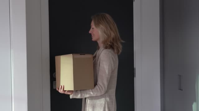 caucasian adult woman at home closing door after receiving a package looking surprised - ricevere video stock e b–roll