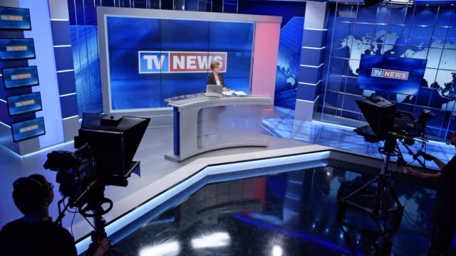 vídeos y material grabado en eventos de stock de presentadora de caucásico cs terminando la presentación de noticias y las luces de estudio salen - periodista
