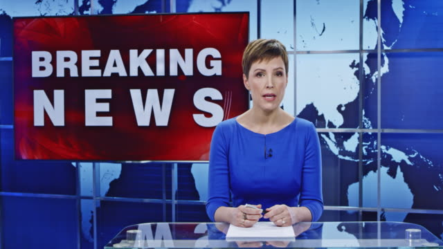 LD Caucasian anchorwoman presenting on latest floods Wide locked down shot of a Caucasian anchorwoman presenting breaking news on the latest floods striking a populated area. The helicopter footage of the area is shown on the screen in the background. Shot in Slovenia. journalist stock videos & royalty-free footage