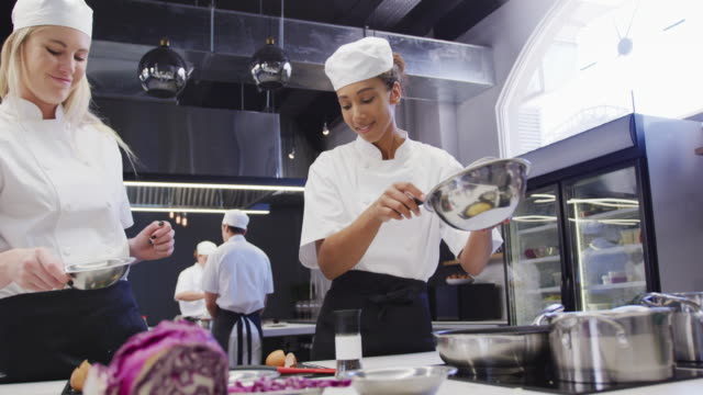 caucasian and african american female chefs in a restaurant kitchen preparing food - busy restaurant kitchen stock videos & royalty-free footage