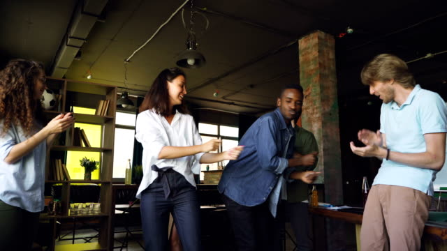 白人とアフリカ系アメリカ人の若い人の同僚は、オフィス パーティーで手をたたくと楽しんで踊っています。現代青年、企業文化や休日の概念。 ビデオ