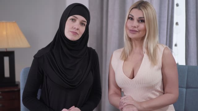 caucasian and muslim women looking at camera and smiling. blond modern woman in candid dress and muslim lady in black hijab posing indoors. cultural diversity, tolerance. - abbigliamento modesto video stock e b–roll