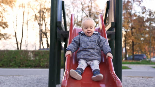 caucasian baby boy on a slide in a park - scivolo video stock e b–roll