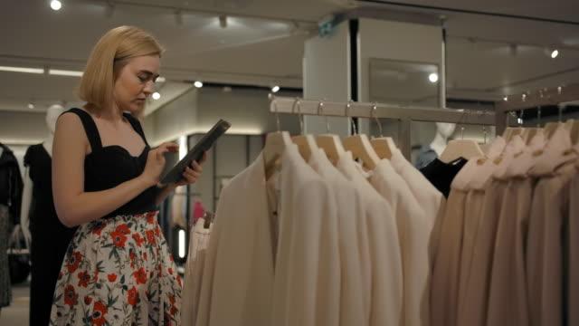 Caucasian blond female examining clothes in shop