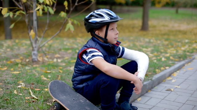 Caucasian boy sitting on the border with his skate Caucasian boy with broken arm sitting on the border with his skate one boy only stock videos & royalty-free footage