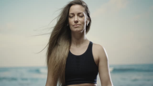 caucasian brunette middle aged woman meditating at the beach. Sea in the blurred out background. 4k, slow motion, handheld beautiful woman meditating resting stock videos & royalty-free footage
