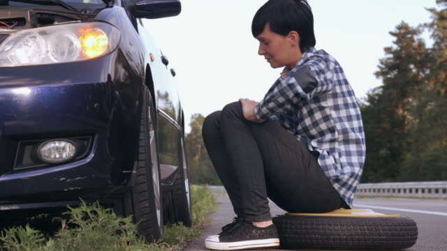 Caucasian brunette try to change a tire outdoors. video