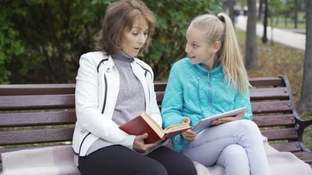 Caucasian brunette woman with a book sitting on the bench with her teenage blond daughter