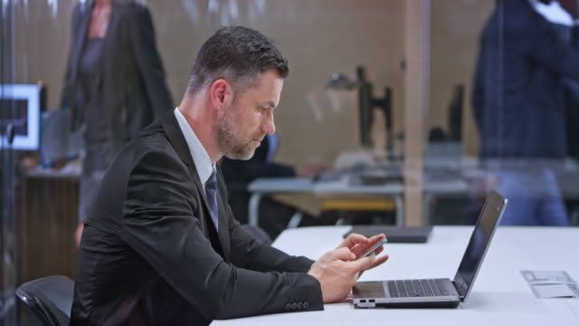 DS Caucasian business man sitting in the glass conference room with his laptop open and checking his mobile phone