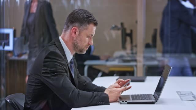 ds kaukasiska affärsman sitter i glas konferensrummet med sin laptop som är öppna och kontrollera sin mobiltelefon - kostym sida bildbanksvideor och videomaterial från bakom kulisserna