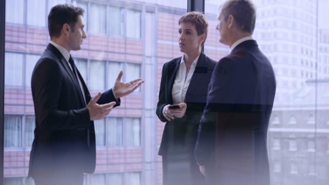 uomo d'affari caucasico che parla con un uomo d'affari anziano e una donna d'affari nell'ufficio di vetro in centro - 20 o più secondi video stock e b–roll