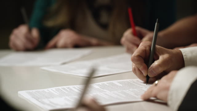 Caucasian Business People's Hands Sign Documents at a Conference Table Indoors