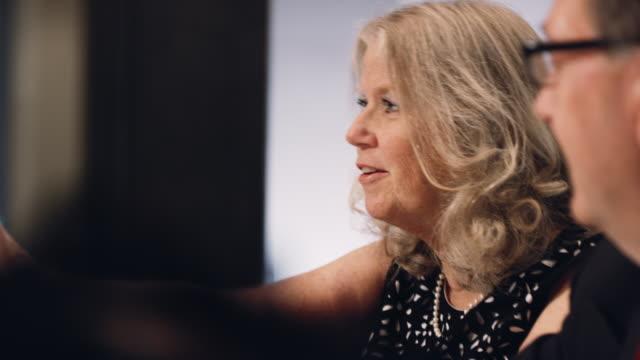 eine kaukasische geschäftsfrau in ihren sechziger jahren lächelt und spricht mit ihren kollegen in einem vorstandszimmer - konferenztisch stock-videos und b-roll-filmmaterial