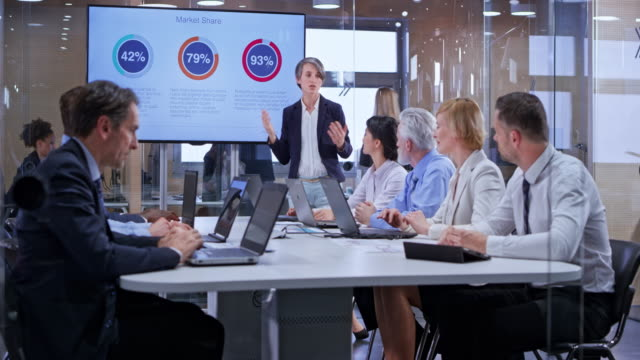 ds caucasian business woman using the display in the glass conference room during her presentation - collega d'ufficio video stock e b–roll