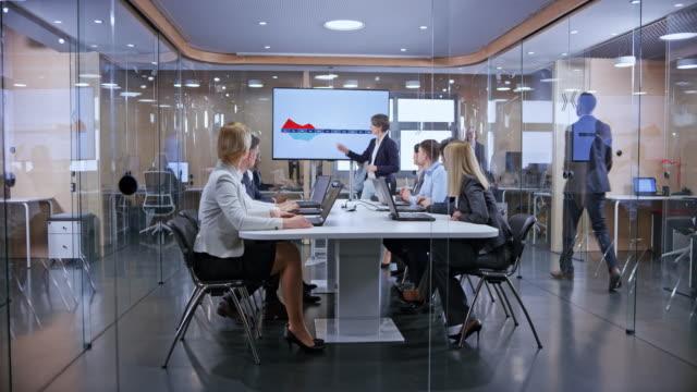 ds kaukasiska affärskvinna med grått hår håller en presentation i glas konferensrummet - affärskonferens bildbanksvideor och videomaterial från bakom kulisserna