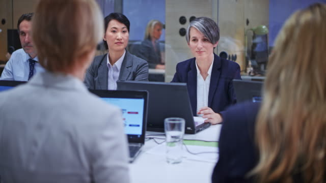 caucasian business woman with grey hair leading a meeting in the conference room - business woman video stock e b–roll