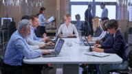 istock DS Caucasian business woman with shorter blonde hair leading a meeting in the glass conference room 1036955870