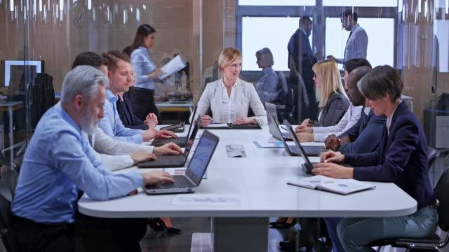 ds 白種人的婦女與較短的金髮領導會議在玻璃會議室 - 管卡規格 個影片檔及 b 捲影像